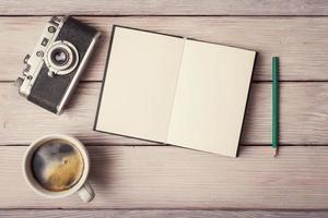 retro kamera, öppen minnesbok och en kopp kaffe foto
