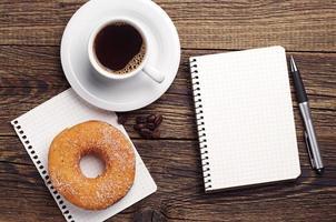 anteckningsblock och kaffe med munk foto