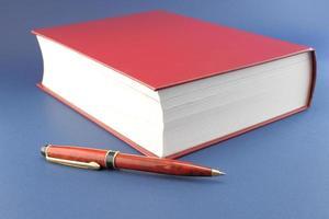 penna och röd bok foto