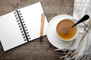 öppen anteckningsbok och kopp te foto