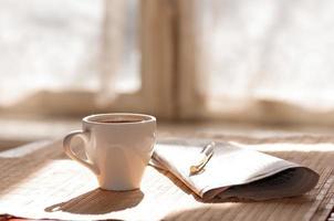 kopp svart kaffe, tidning och en penna foto