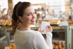 kvinna som kontrollerar sin inköpslista foto
