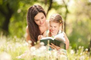 mor och dotter som läser i gräsbevuxen park foto