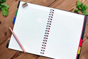 öppnad spiral anteckningsbok med penna och slipare, ekollon foto
