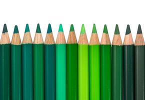 isolerad rad med grönfärgade kritor foto