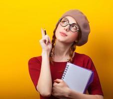 rödhårig tjej med anteckningsbok och penna på gul bakgrund. foto
