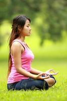 flicka gör meditation på stranden foto