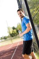 ung idrottsman som tar en paus på en varm sommardag foto