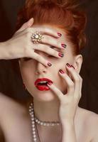 skönhet stilig rödhårig kvinna med frisyr bär smycken foto