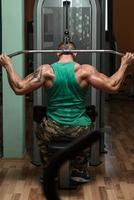 kroppsbyggare som gör tungvård mot rygg foto