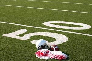 amerikansk fotboll, hjälm och pom poms på fältet foto