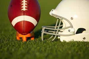 amerikansk fotboll och hjälm på fältet foto