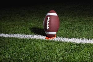 college fotboll på tee på natten foto