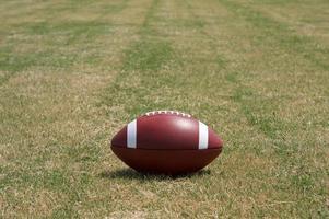 amerikansk fotboll på gräset foto