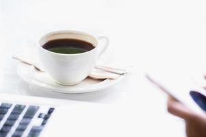 kaffebärbar dator och hand av affärskvinna foto