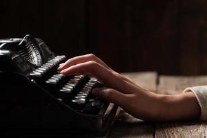 händer som skriver på gammal skrivmaskin över träbakgrund foto