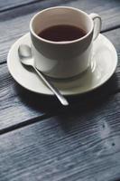 kopp te på träbord foto