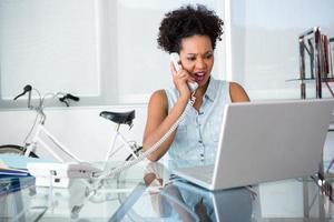 avslappnad ung kvinna som använder telefon och bärbar dator