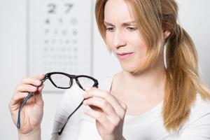 tittar på nya glasögon foto
