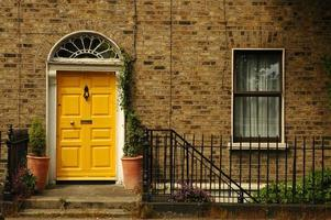 ingången till ett tegelhus med en gul dörr