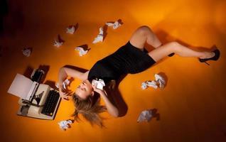 vacker flicka ligger vid skrivmaskinen. foto