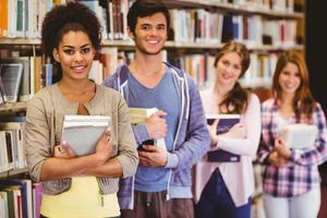glada studenter som håller böcker i rad foto