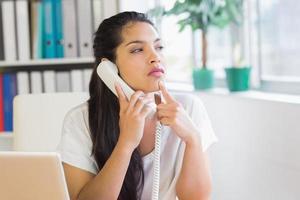 tankeväckande affärskvinna med fasttelefon foto