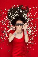 tjej med 3D-glasögon och popcorn som tittar på en film foto
