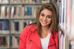 porträtt av glad leende ung brunett studentflicka foto