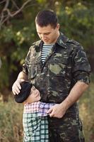 liten pojke och soldat i en militär uniform foto