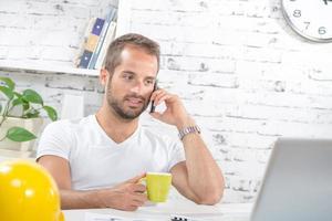 ung affärsman som dricker en kopp kaffe foto