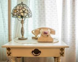 retro telefon med vintage lampa på träbord nära fönster.