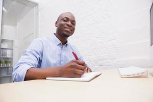 porträtt av en leende affärsman som skriver anteckningar foto