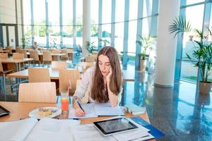 tjej studerar i universitetets kantine med färsk och kaka foto