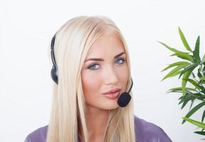 vacker blond, kvinnlig kundtjänstoperatör som använder headset foto
