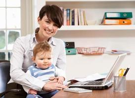 kvinna med barn som arbetar hemifrån med laptop foto