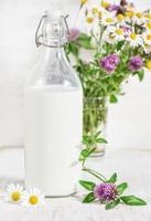 färsk mjölk i gammaldags flaska och vilda blommor foto