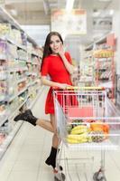 förvånad kvinna som shoppar i stormarknaden foto