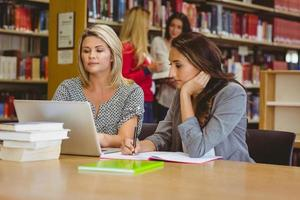 fokuserade studenter på bärbar dator med klasskamrater bakom sig foto