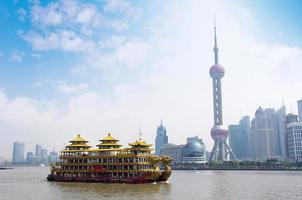 drakbåt genom shanghai skyline foto