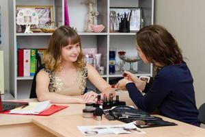 makeupartist visar kunden en ny läppstift foto