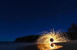 stjärnklar natt stålull på stranden med reflektioner foto