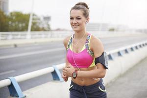 kvinna som joggar över staden foto