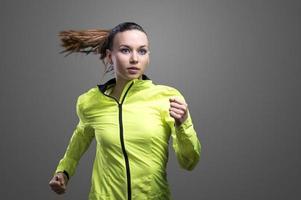vacker kvinnalöpare i grön jacka