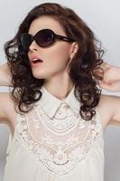 vacker ung brunett med lockigt hår i solglasögon. foto