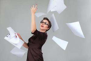 kvinna som kastar papperssidor foto
