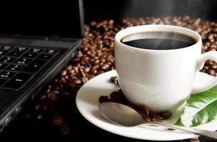 kopp kaffe med dimma, bärbar dator, kaffeblad vid frukosten foto