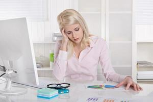 ung blond trainee i rosa blus med huvudvärk vid skrivbordet. foto