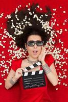 förvånad tjej med 3D-glasögon, popcorn och regissörsklapp foto