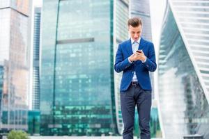 stilig affärsman i kostym med smart telefon i handen foto